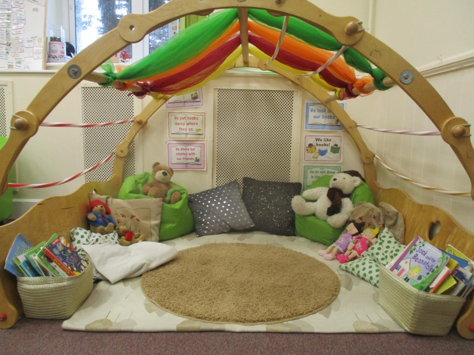 A larger picture of the reading area, showing baskets of books in addition to the cushions and toys.