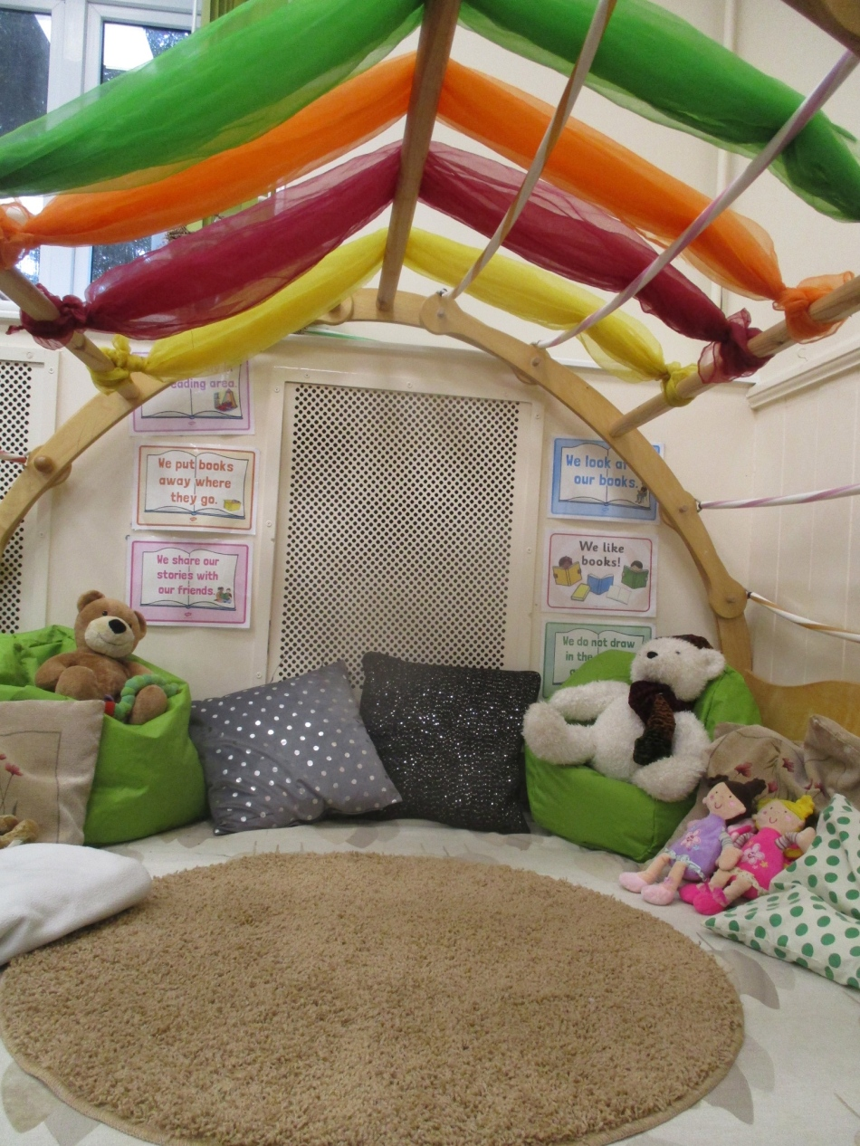 A semi domed reading area, replete with coloured cushions and soft toys.