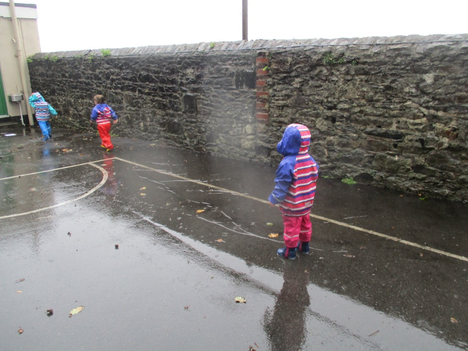 Three children wearing puddle suits playing in puddles in the rain.