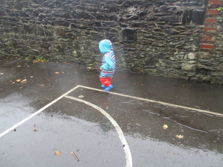Child in blue and red puddle suit splashes in a puddle.
