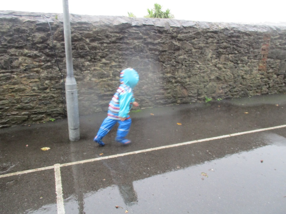 Child in blue puddle suit runs in the rain.